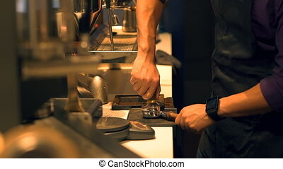 Barista pressing ground coffee into portafilter by tamper to...