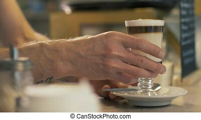 Barista putting prepared coffee latte in glass cup on table...