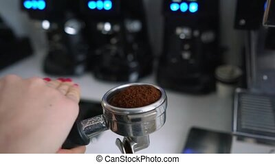 Barista shakes portafilter with ground coffee in cafe for...