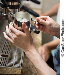Barista Steaming Milk In Coffeeshop - Cropped image of...