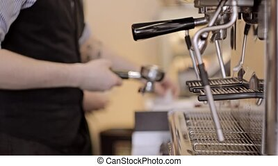 Barista tamping the grind coffee for espresso. Out of focus background.