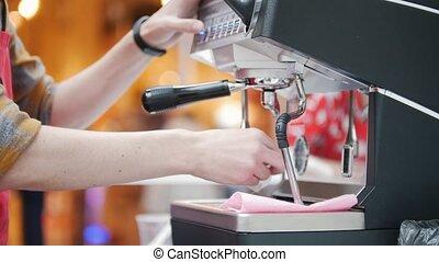 Barista wipes a coffee machine in a coffee shop