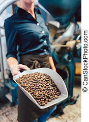 Barista woman with a sample of freshly roasted coffee beans