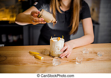 barmaid adds a topper to a white cocktail with orange peel