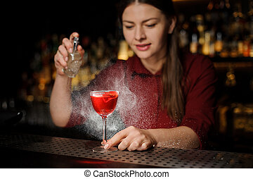 barmaid adds peat whiskey to alcoholic cocktail