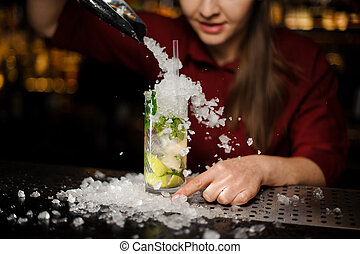 barmaid adds to mojito crushed ice