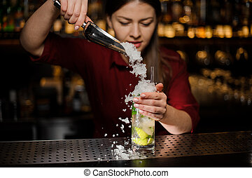 barmaid adds to mojito in a crystal glass crushed ice