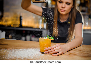 barmaid finishes preparation of cocktail decorated with mint and dried orange