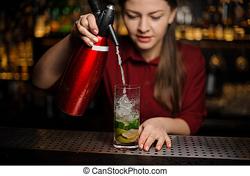 barmaid finishes preparing a mojito, adding soda water to the crystal glass