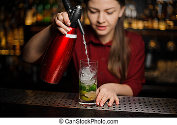 barmaid finishes preparing a mojito alcoholic cocktail, adding soda water