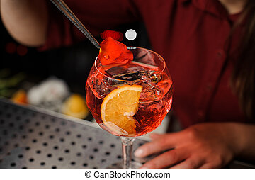 barmaid finishes the preparation of Spritz Veneziano, adding a rose petal