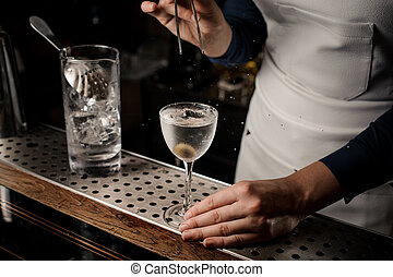 Barmaid hand putting an olive into a cocktail glass