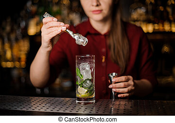 barmaid in a red dress prepares a mojito , adding ice