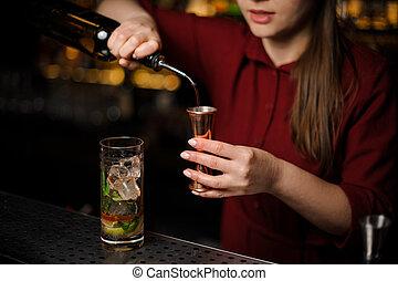 barmaid prepares a mojito, adding dark rum and using bar equipment