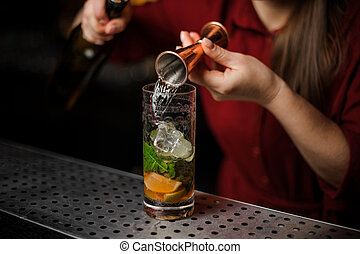 barmaid prepares a mojito, adding white rum