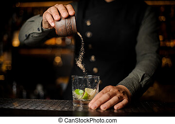 Barman adding a cane sugar into the cocktail glass with lime
