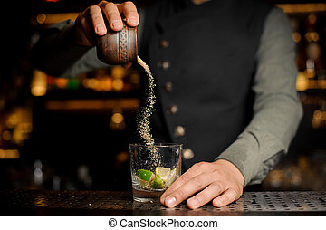 Barman adding cane sugar into the cocktail glass with lime. Process of making Caipirinha cocktail