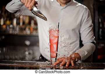 Barman adding ice cubes into the glass with strawberry mojito summer cocktail