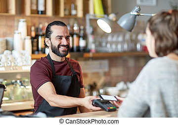barman and woman with card reader and smartphone