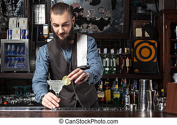 Young happy barman at work preparing cocktail.