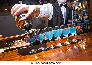 Barman, bartrender, pouring blue coloured drinks from the shaker to the row of glasses on the bar counter, visible fragment of the hand, shaker and barman. No need model relase.