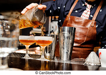 barman completes the preparation of two alcoholic cocktails using bar equipment