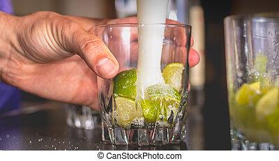 barman crushes green lemons with a pill to make caipirihnas