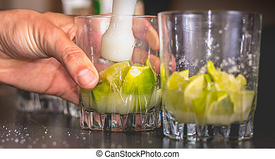 barman crushes green lemons with a pill to make caipirihnas