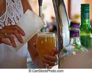 Barman hands pouring draught beerfrom a tap