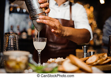 Barman in a brown leather apron pouring alcoholic cocktail into the glass