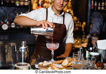 Barman in a brown leather apron pouring fruit alcoholic cocktail into the glass