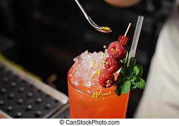 Barman is decorating cocktail with rasberry no face