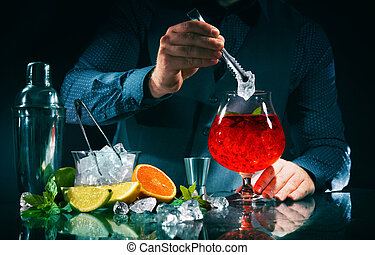 Barman is making campari orange cocktail at night club