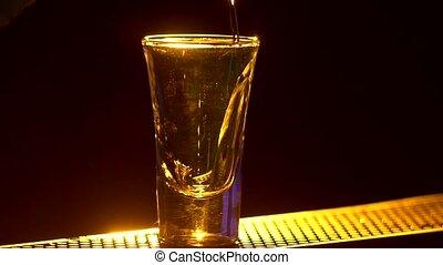 Barman is making cocktail and at edge of bar counter, shots,...