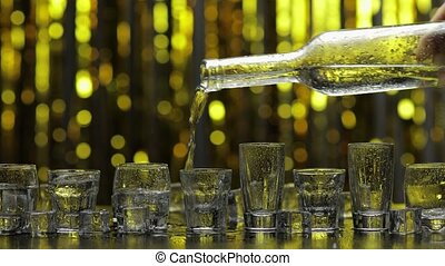 Bartender pouring up frozen vodka from bottle into eight shots glasses with ice cubes against shiny gold party celebration background. Barman pour of cold transparent alcohol drink vodka tequila