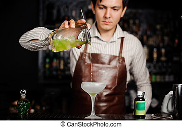 Barman pouring a cocktail into glass