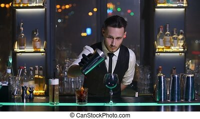 Barman pouring alcoholic drink feom shaker - Handsome...