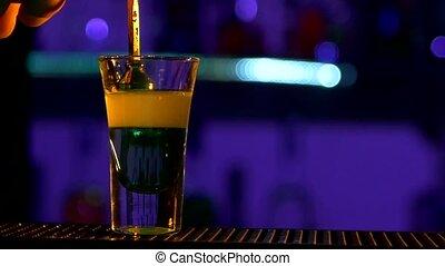 Barman pouring clear alcohol liquid, liquor, cloudy, into a...