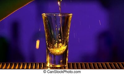 Barman pouring clear alcohol liquid with splash, into a glass,  shots, slow motion, close up