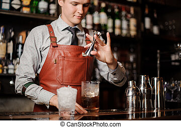 barman pouring cocktail in a glass