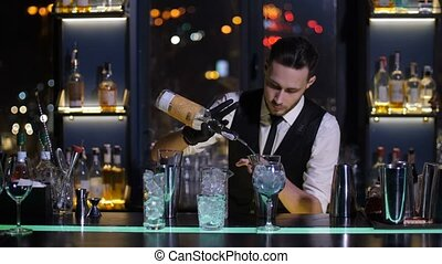 Barman pouring liquor from bottle in jigger at bar -...