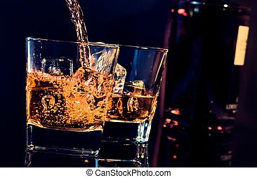 barman pouring whiskey in front of whiskey glass and bottle