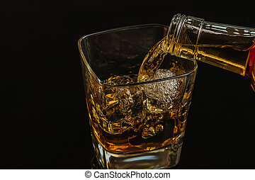barman pouring whiskey with ice cubes in glass on black background, cool atmosphere