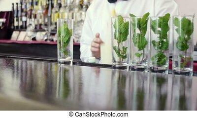 barman preparing mojito cocktail - Close-up of male barman...