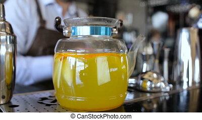Barman preparing teapot with tea in the bar