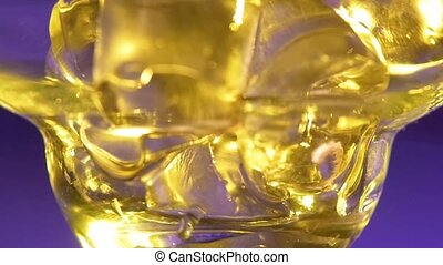 Barman puts ice in glass, pouring alcohol liquid, close up, slow motion