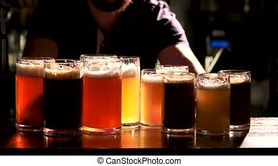 Barman serves up glasses of draft beer. Bartender put many...