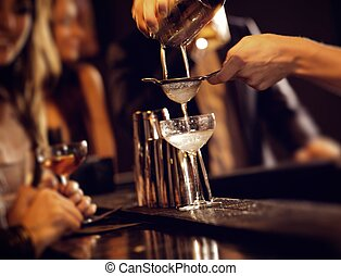 Barman pouring wine from shaker and serving it