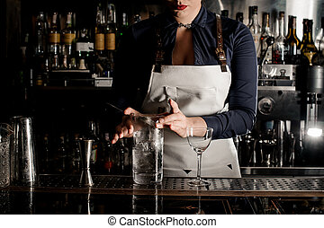 Barman woman with deep neckline stirring cocktail with ice...