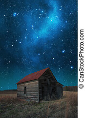 Red roof barn before the milky way galaxy.